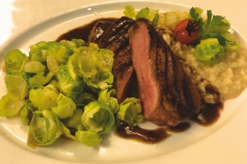 Pink fried duck breast with risotto and Brussels sprouts